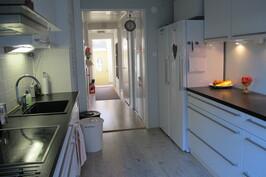Keittiö ja alakerran käytävä, jossa liukuovi-kaappi ja wc