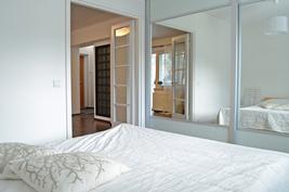 Koko seinän levyiset peiliovet kätkevät sisälleen paljon säilytystilaa ja ovat kaunis yksityiskohta.