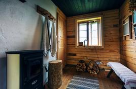 Saunan pukuhuoneessa on puulattia ja kamina. Terassi pukuhuoneesta josta näkymä merelle