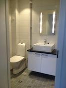 Tilava kylpyhuone. Lattialämmitys, Tulikiven vuolukivellä laatoitettu lattia.