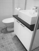Pesuallaskaappi korkeakiilto-valkoinen, allastaso mustaa graniittia malja-altaalla.