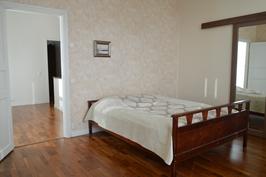 Yläkerran iso makuuhuone. Oikealla peilien takana tilava vaatehuone