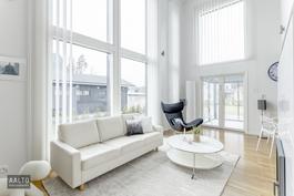 Kahden kerroksen korkuinen olohuone, jossa suuret ikkunat