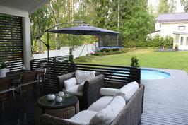 Viihtyisä terassi suoraan olohuoneesta takapihalle on ihana lisä upeaan taloon.