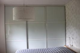 Makuuhuoneen maitolasiset liukuovikomerot seinän mittaisina