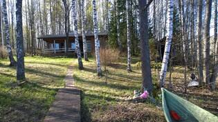 Laiturilta mökille, sauna häämöttää oikealla puolella