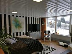 Alakerran makuuhuone, jonka suurista ikkunoista näkymä omalle pihalle. Huoneesta ovi alaterassille.