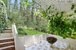Näkymä olohuoneen edessä olevalta katetulta terassilta puutarhaan.