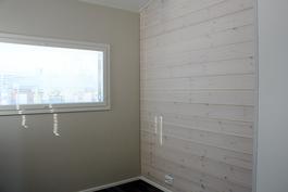 Makuuhuoneessa on tehosteseinänä valkolakattu hirsipaneeli (kuva valmistunut kohde)