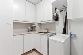 Kodinhoitohuone, pesukoneelle tilaa  ja pesuallas, paljon kaappeja