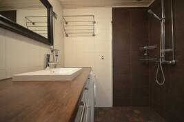 Alakerran kylpyhuone, jossa liikutettava suihkuseinämä
