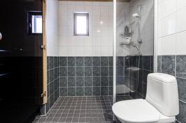 Pesuhuone kaakelipinnoin, suihkuseinä estää roiskeilta.