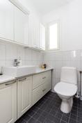Alakerran erillinen wc, valkea kalustus.