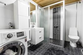 Paikka pyykkikoneelle, valkea kalustus ja wc.