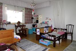 Tilava lähes olohoneen kokoinen makuuhuone.