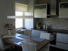 Keittössä Puustellin kokonaisuus: rungot tummasuklaa, ovet korkea kiiltoinen valkoinen.