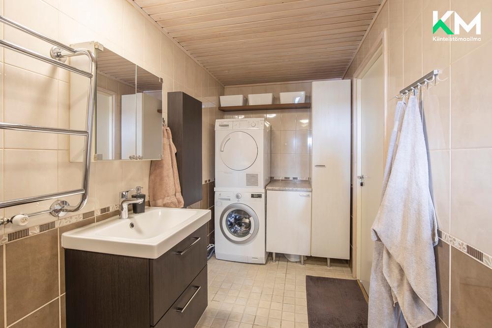 Kylpyhuoneen toiseen päähän on toteutettu tehokas kodinhoitopiste.