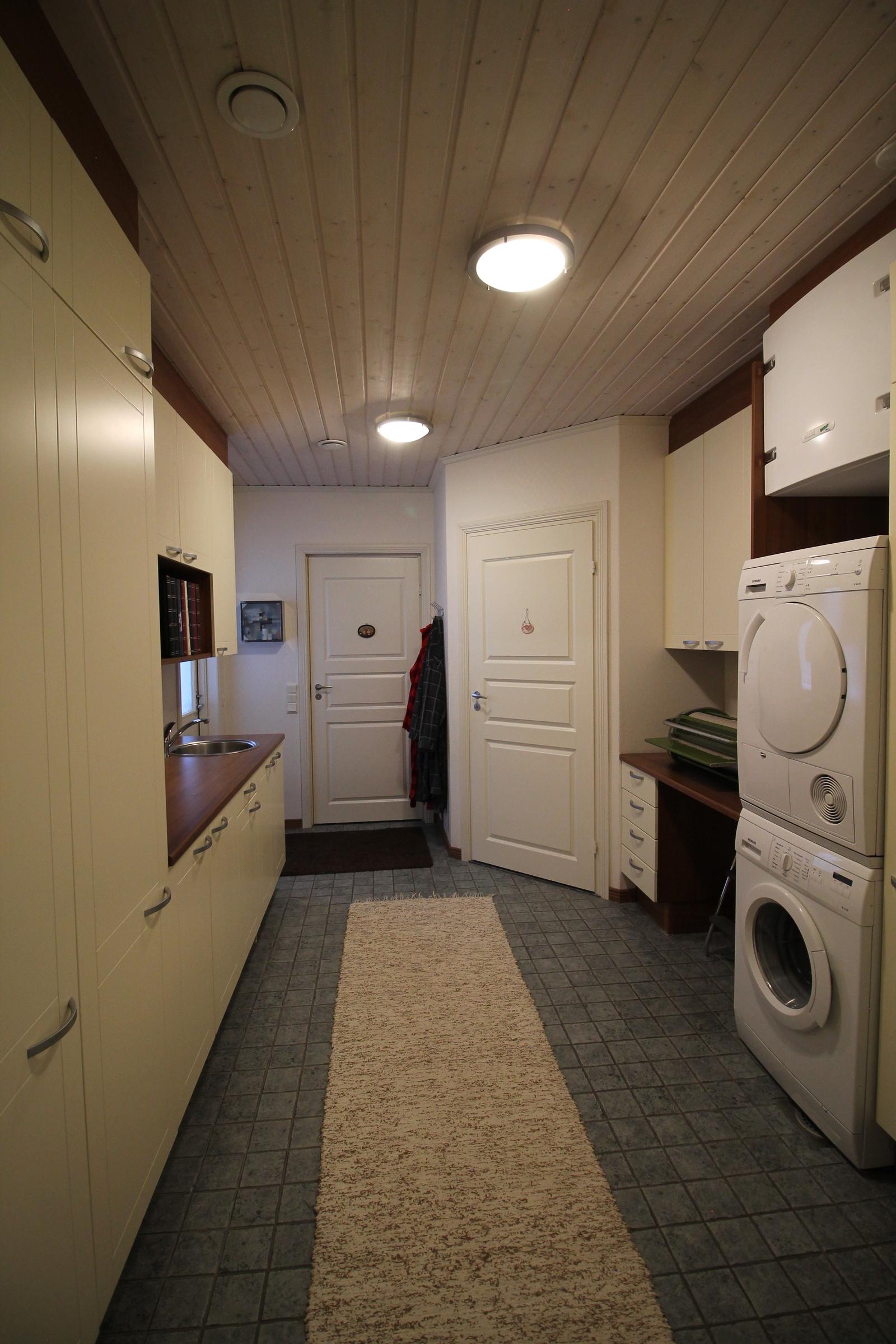 Kodinhoitohuone toisesta suunnasta. Päässä olevan oven takana on kylpyhuone. Pääsy myös ulos.