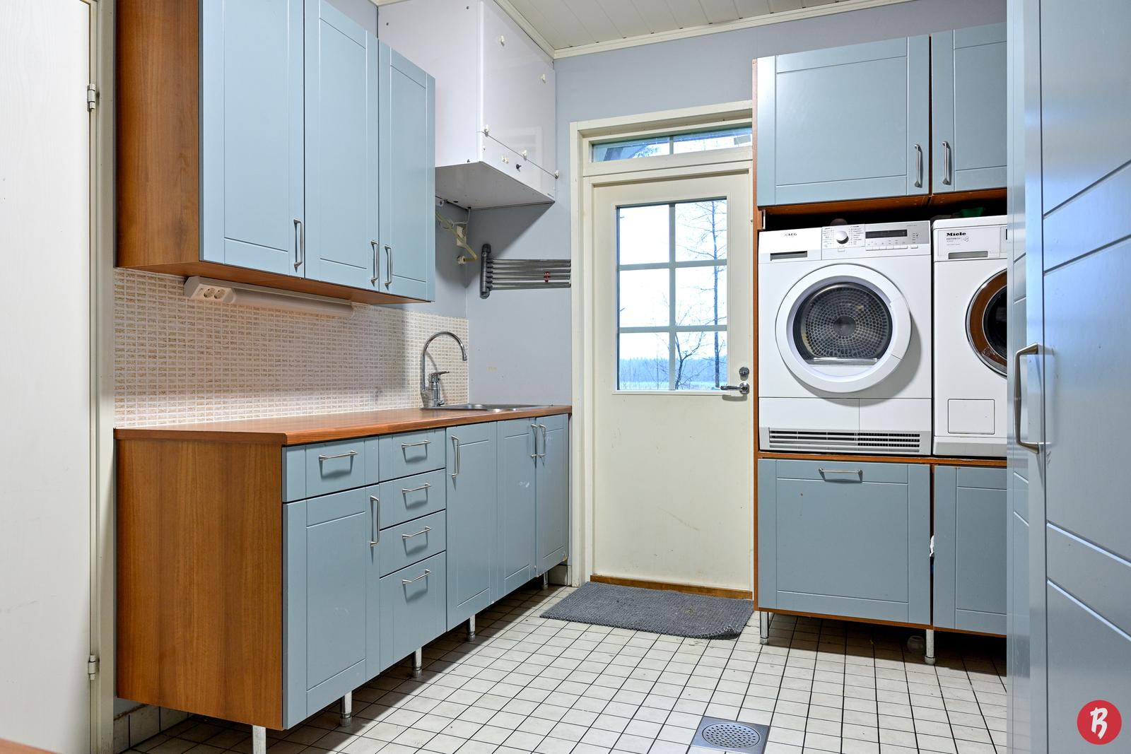 Kodinhoitohuone ja kulku takapihalle, jossa suuri pyykinkuivausteline. Oikealla ovi kuivaushuoneeseen ja vaatehuoneeseen. Vasemmalla ovi pesuhuoneeseen.