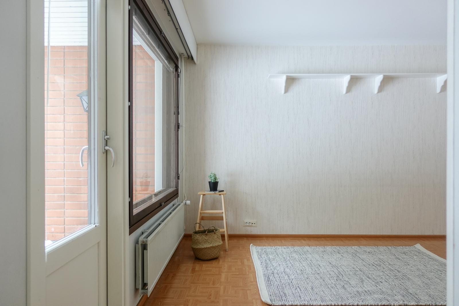 Olohuoneen yhteydestä käynti laatoitetulle terassille ja takapihalle