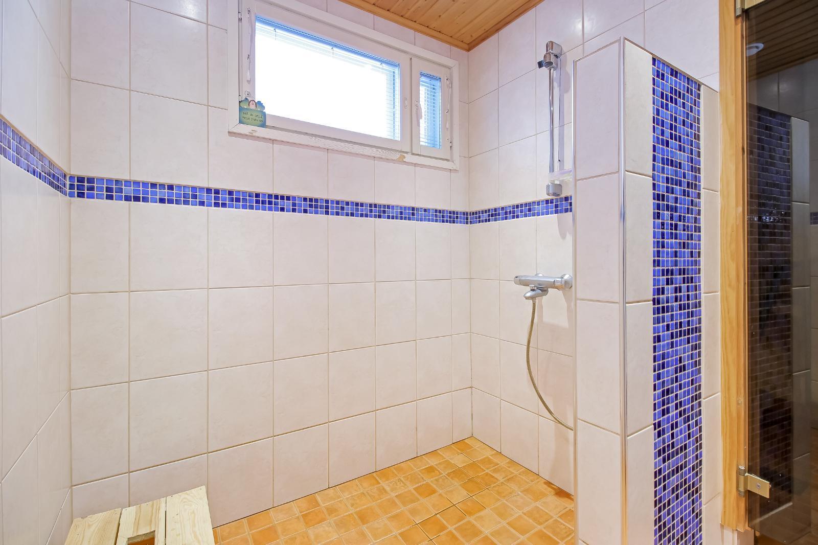 Suihkuseinä ja ikkuna kylpyhuoneessa.