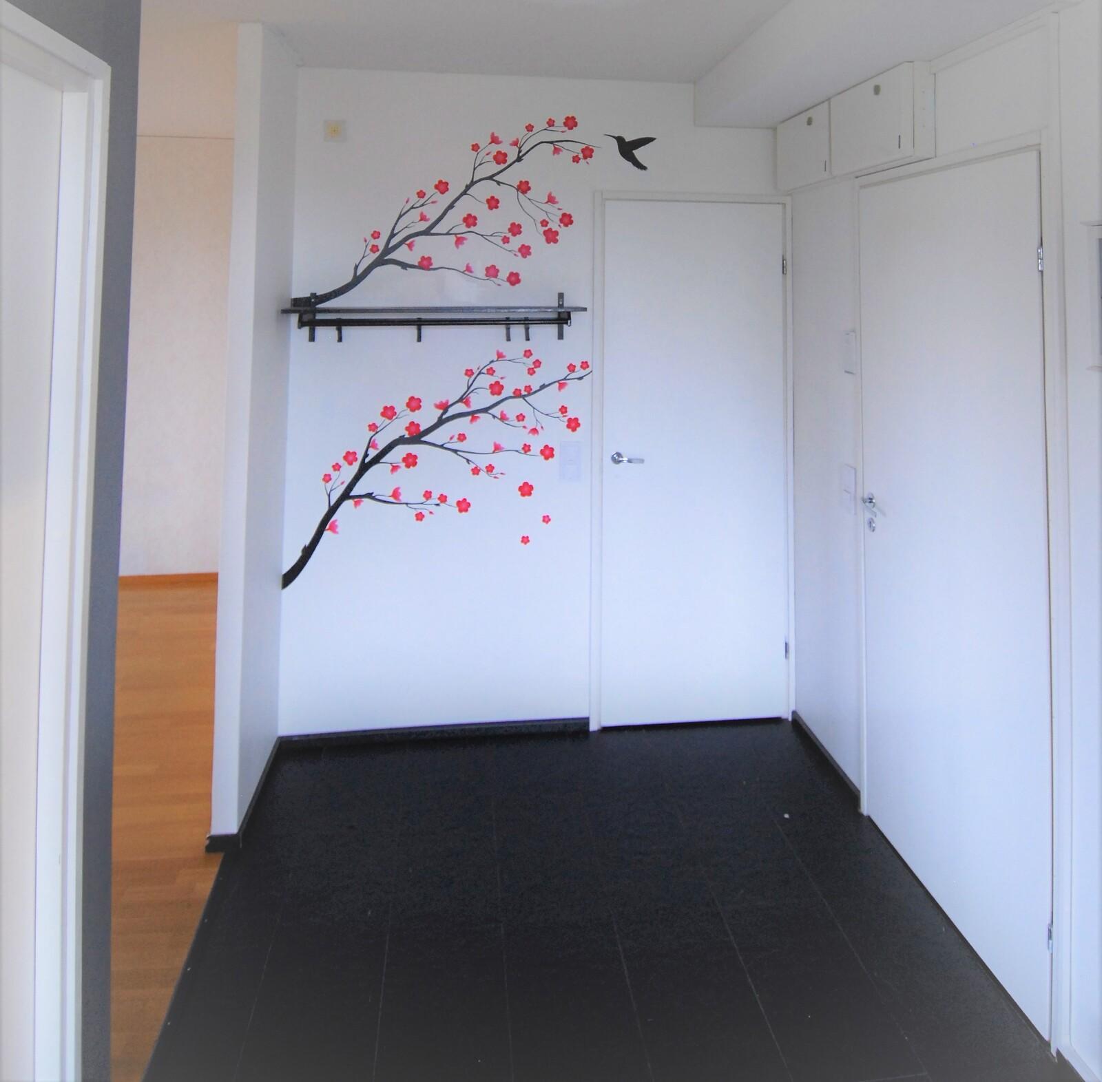 Eteisen kirsikan oksat ovat käsinmaalatut. Ulko-ovi on oikealla.