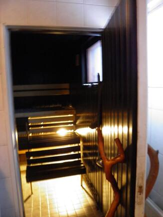 Tummasävyinen sauna, jossa puukiuas