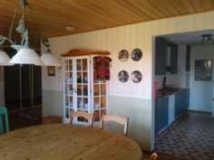 Ruokailuhuone on tilava. Taustalla keittiö.
