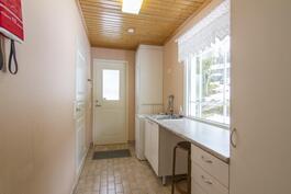 Kodinhoitohuoneesta kulku ulos, kylpyhuoneeseen ja keittiöön.