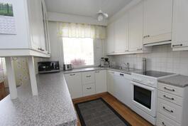 Kodikkaassa keittiössä runsaasti kaappitilaa ja laskutasoa.