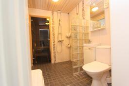 Ajattomin materiaalivalinnoin sisustetussa kylpyhuoneessa kaksi suihkua.