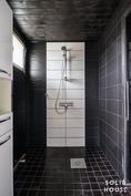 Tumman tyylikäs kylpyhuone.
