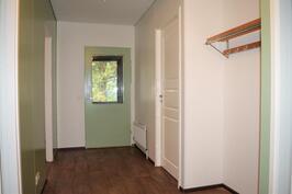 Kylpyhuoneen ovelta. Oikealla kaksi makuuhuonetta, joiden välissä yhteinen vaatehuone. Vasemmalla olohuone ja keittiö