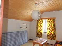Yläkerran II makuuhuone. Katot ovat paneloidut ja seinissä on kangastapetti