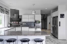 Hyvinvarusteltu keittiö integroiduilla kondinkoneilla