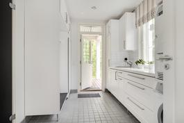 Kauniin valkoinen kodinhoitohuone/ Vackert, vitt hjälpkök med en utgång