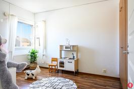 Valoisa makuuhuone, jonka nurkassa ikkunat kahteen ilmansuuntaan luovat avaruutta.