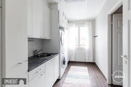 Kodinhoitohuone 7,5m² alakerrassa. Valkoiset kaapistot, tilaa pesutornille, allas ja pöytätasoa