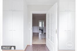 Sisäänkäynti lämpimältä kuistilta, jossa laattalattia ja valkoiset kaapistot