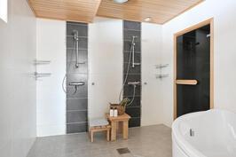 Tilavassa kylpyhuoneessa on kaksi suihkua ja iso amme.