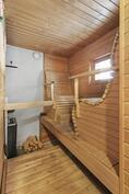 Sauna, jossa puukiuas ja varaus sähkökiukaalle