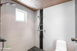 Vaalean sävyinen kylpyhuone, jossa kaksi suihkua..