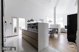 Keittiö, ruokailutila ja olohuone 53,2m². Saarekkeessa uuni, kaapistot molemmin puolin