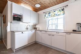 Keittiössä puuhastellaan ikkunasta tulevan valon äärellä