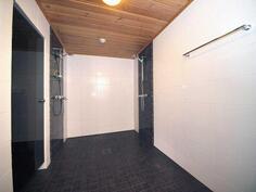 Alakerran ihanan iso kylpyhuone kahdella suihkulla.