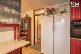 Keittiön toisella seinämällä on työskentely- ja laskutilaa sekä lasikaapistoissa säilytystilaa.