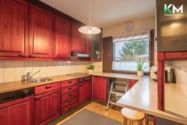 Keittiössä tila on hyödynnetty tehokkaasti. Keittiökaapit ovat puuta. Harmahtavat, modernit lasiovet jäävät oikealle.