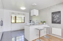 Upea valkoinen keittiö osittain integroiduilla kodinkoneilla
