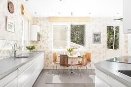 Keittiössä on valkoiset kaapistot ja runsaasti ruuanvalmistus- ja säilytystilaa.
