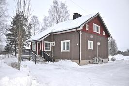 Talo sisäänkäynnin puolelta, lunta satelee